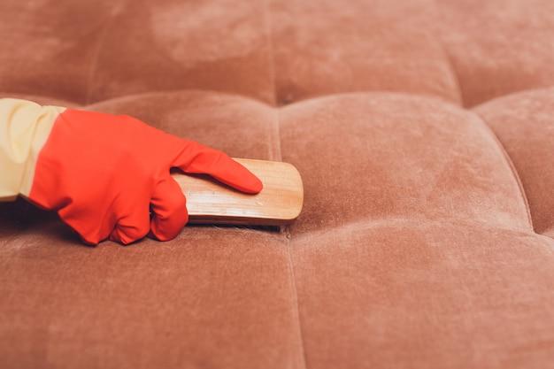 Manos femeninas con un cepillo limpiando el sofá