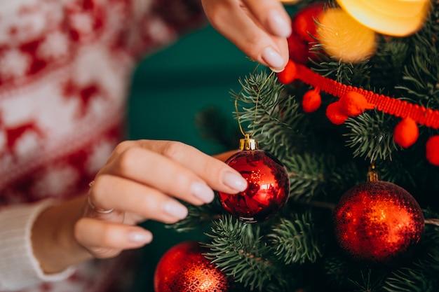 Manos femeninas de cerca, decorando el árbol de navidad con bolas rojas
