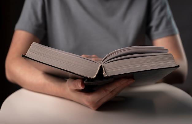 Manos femeninas de cerca, sosteniendo y leyendo libros o libros de texto en tapa dura.