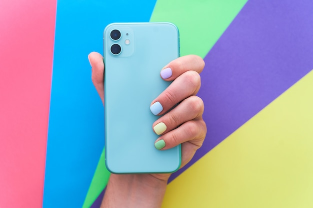 Manos femeninas con colores brillantes sosteniendo un teléfono