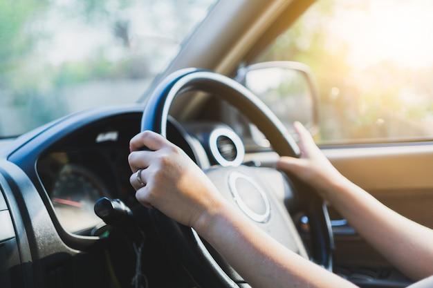 Manos femeninas conduciendo en su coche.