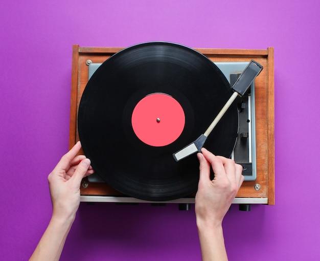 Manos femeninas configurar reproductor de discos de vinilo retro con placa sobre fondo morado