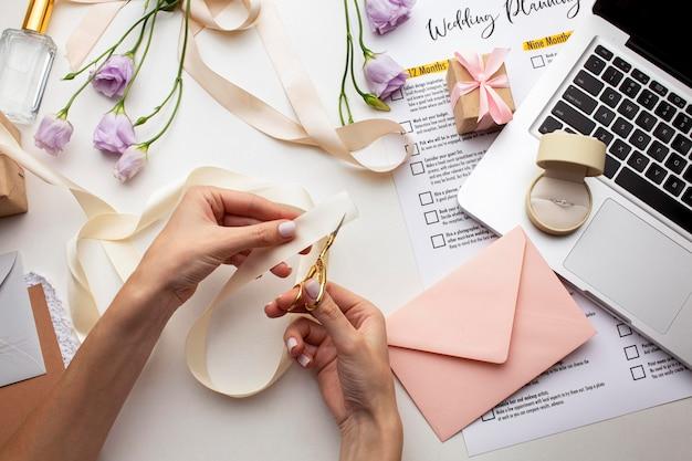 Manos femeninas creando invitaciones hechas a mano