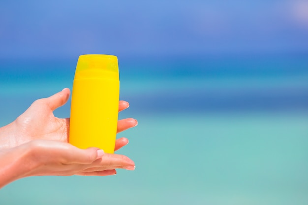 Manos femeninas con crema solar botella mar azul