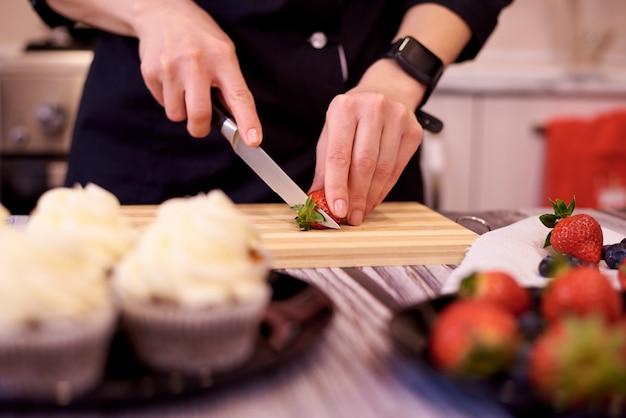 Manos femeninas con un cuchillo cortan fresas en tabla de cortar en la mesa de la cocina. cocinar pastelitos con fresas y arándanos.