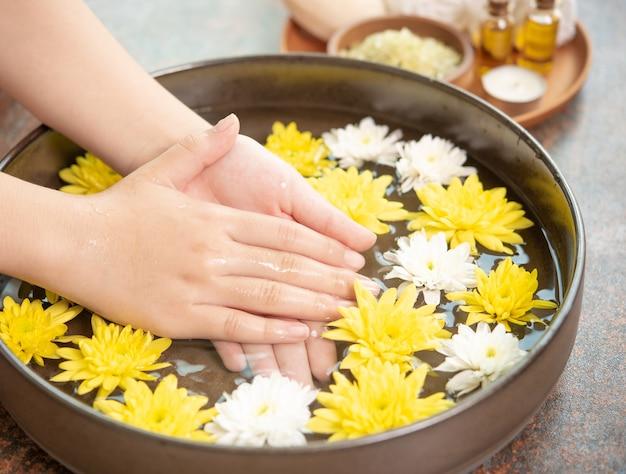 Manos femeninas y cuenco de agua de spa con flores, de cerca. manos spa.