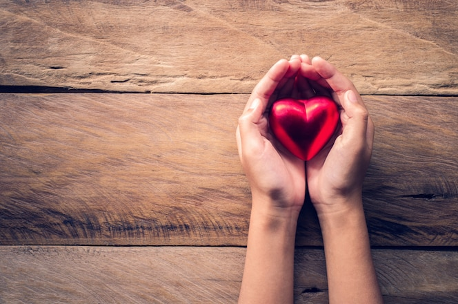 Manos femeninas dando corazón rojo