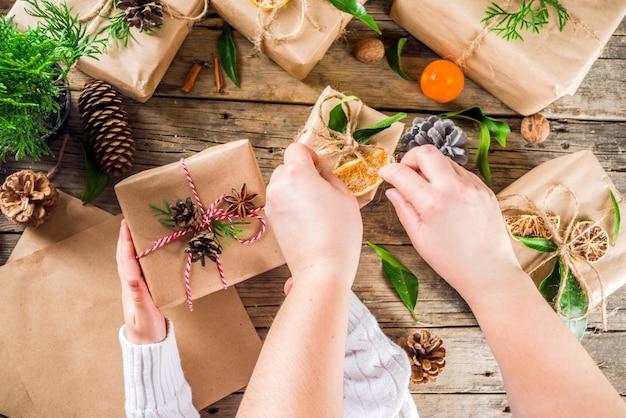 Manos femeninas decoran caja de regalo de navidad.