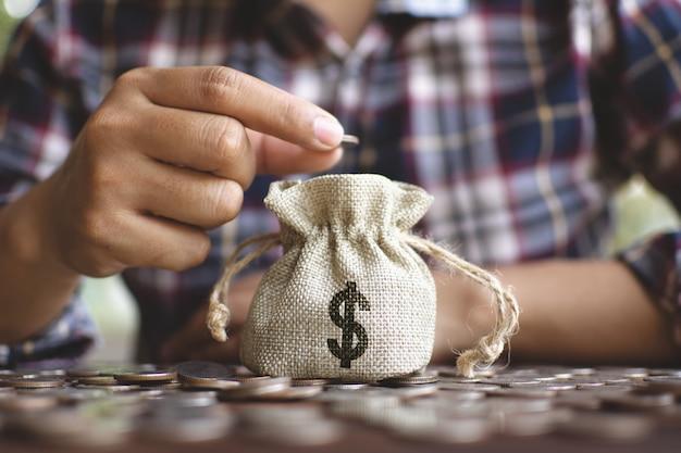 Manos femeninas dejando caer el dinero en la bolsa ahorrando dinero.