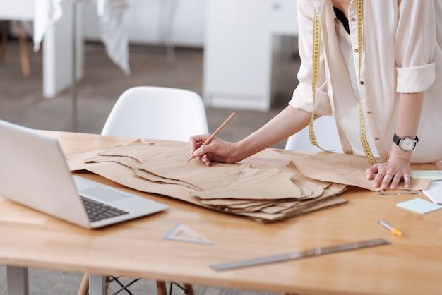 Manos femeninas delicadas y elegantes sosteniendo un lápiz y escribiendo en patrones de vestimenta acostado sobre una mesa de trabajo con una computadora portátil.