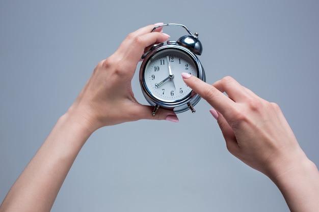 Las manos femeninas y el despertador de estilo antiguo en gris