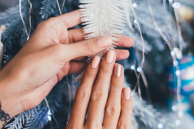 Manos femeninas con diseño de uñas de año nuevo de navidad. manicura de esmalte de uñas beige nude, un dedo bronce dorado brillante