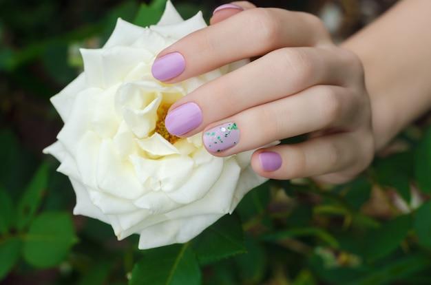 Manos femeninas con diseño de uñas lila