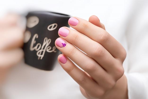 Manos femeninas con diseño de uñas rosa sosteniendo la taza negra.