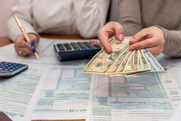 Manos femeninas con dólar y formulario de impuestos 1040