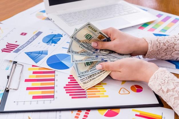 Manos femeninas con dólar sobre fondo de gráficos de negocios