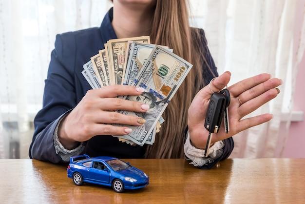 Manos femeninas con dólares, coche y llaves