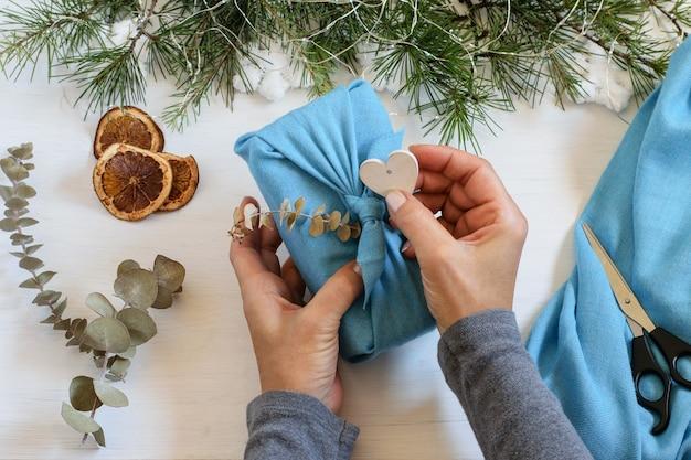 Manos femeninas embalaje envoltura de regalo de navidad en tela reutilizable. regalo envasado en estilo furoshiki.