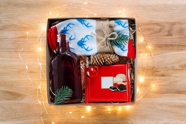 Manos femeninas embalaje regalo de navidad en mesa de madera
