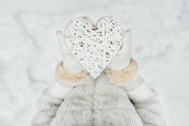 Manos femeninas en mitones de punto blancos con un corazón blanco romántico vintage entrelazado