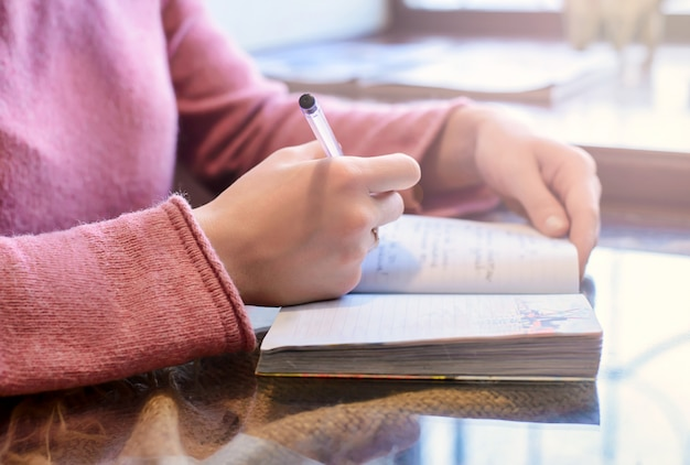Manos femeninas escriben en un bloc de notas de papel
