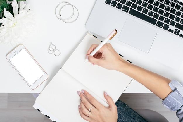 Manos femeninas escriben en el cuaderno sobre una mesa blanca con un teclado y un teléfono con pantalla en blanco