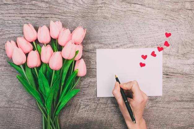 Las manos femeninas escriben un mensaje de amor en un sobre blanco, sobre un fondo de madera. día de san valentín