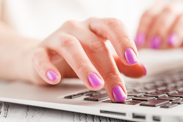 Manos femeninas escribiendo en la computadora portátil, en la pared brillante