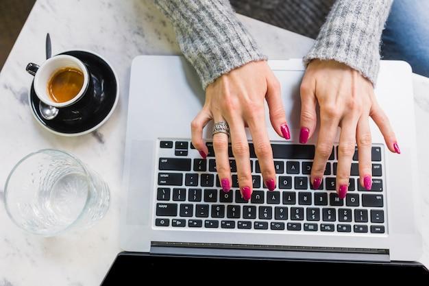 Manos femeninas escribiendo en la computadora portátil