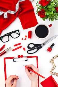 Las manos femeninas escribiendo contra objetos de moda mujer