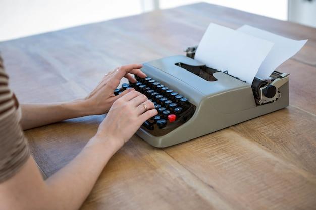 Manos femeninas escribiendo en una máquina de escribir que está en un escritorio de madera