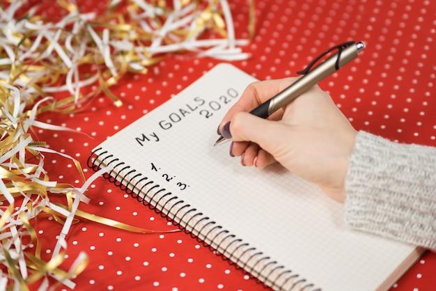Manos femeninas escribiendo my goals 2020 en un cuaderno.
