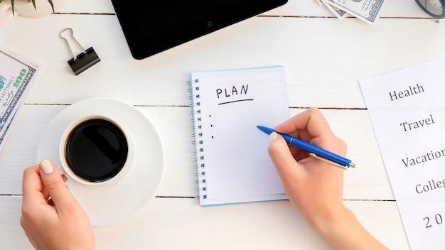 Manos femeninas escribiendo un plan de tareas en un bloc de notas, sosteniendo un café. tableta, dinero. fondo de madera