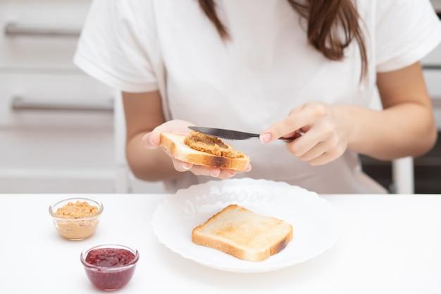 Manos femeninas esparcir pasta de mantequilla de maní en pan