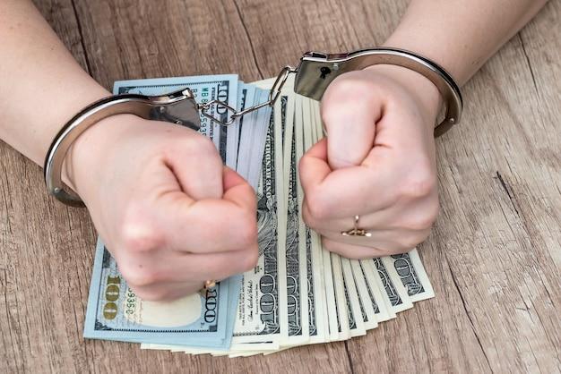 Manos femeninas esposadas en billetes de dólar
