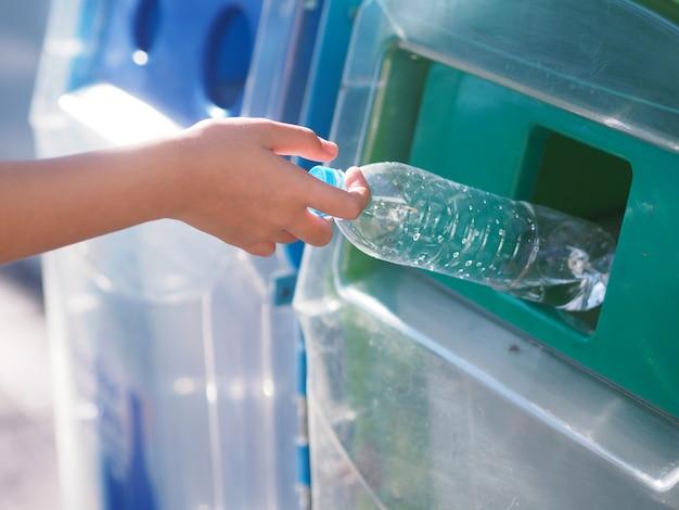 Las manos femeninas están tirando la botella de plástico a la basura.