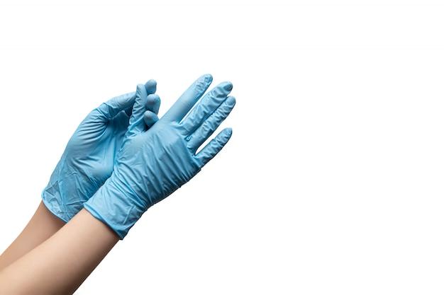 Manos femeninas en guantes desechables sobre fondo blanco.