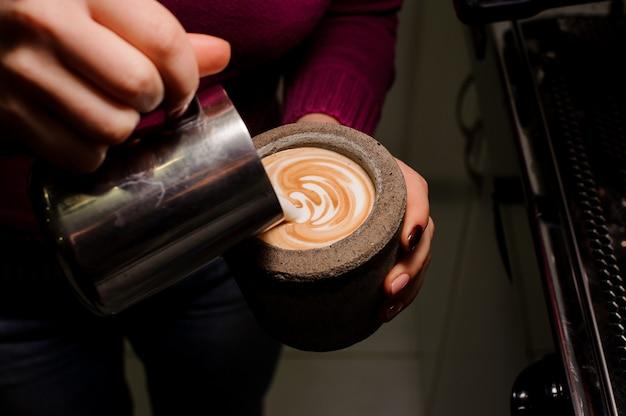 Manos femeninas haciendo arte latte en la olla de hormigón