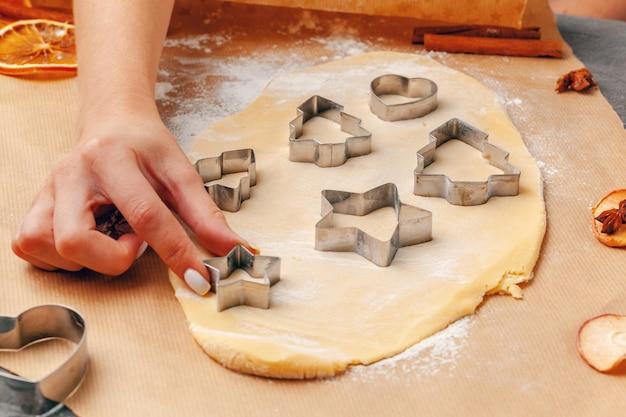 Manos femeninas haciendo galletas de masa fresca en casa