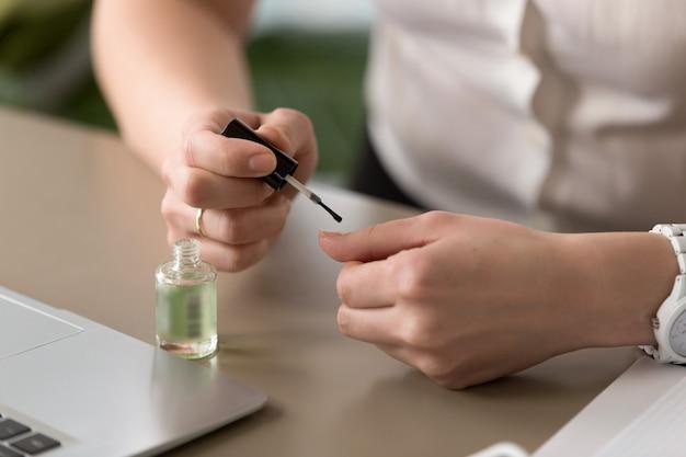 Manos femeninas haciendo manicura en la oficina, pintando uñas, de cerca