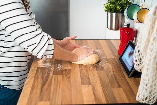 Manos femeninas haciendo masa para pizza