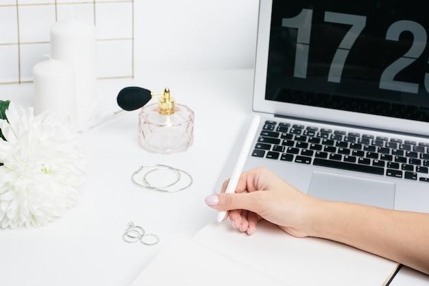 Manos femeninas haciendo notas en un bloc de notas sobre una mesa blanca con un teclado portátil