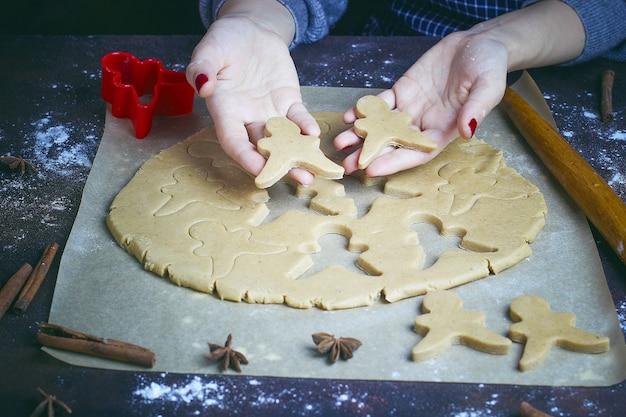 Manos femeninas en harina haciendo galletas de navidad en forma de hombre de jengibre de masa en la cocina
