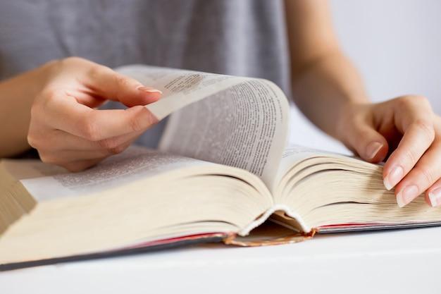Manos femeninas hojeando páginas de libros. concepto de lectura
