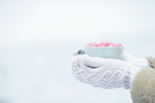 Manos femeninas holdink blanco taza de café con malvaviscos blancos y rosados