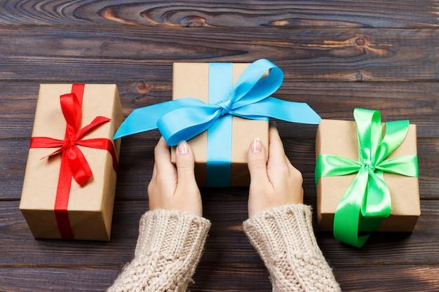 Manos femeninas jovenes que sostienen los regalos con la cinta colorida