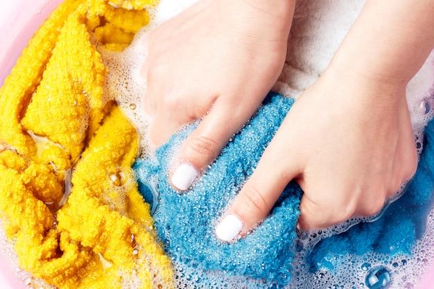 Manos femeninas lavar ropa multicolor en cuenca, vista superior