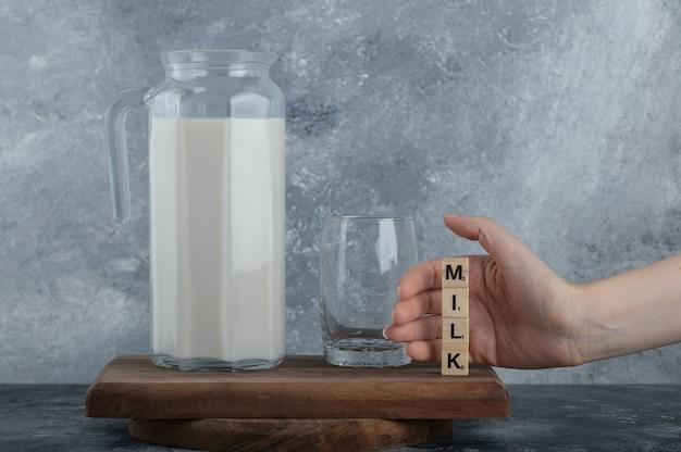 Manos femeninas con letras de madera con leche fresca.