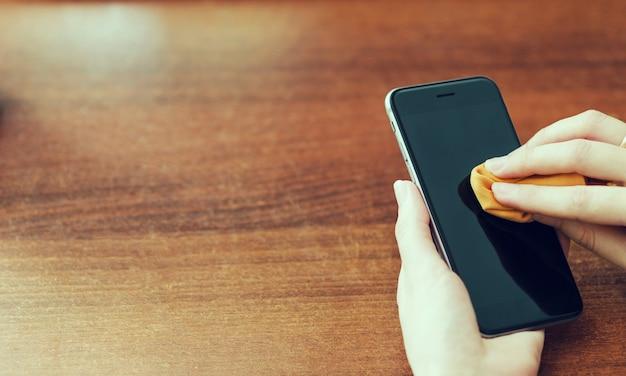 Las manos femeninas limpian la pantalla del teléfono inteligente con un paño naranja.