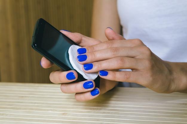 Manos femeninas limpian el polvo de la pantalla táctil del teléfono móvil